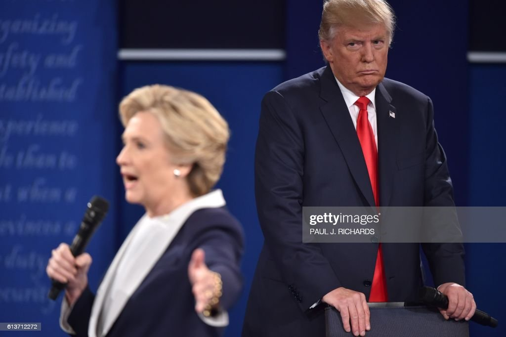 TOPSHOT - Republican presidential candidate Donald Trump listens to Democratic presidential candidate Hillary Clinton during the second presidential debate at Washington University in St. Louis, Missouri on October 9, 2016. / AFP / Paul J. Richards