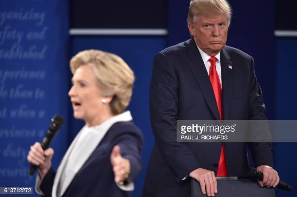 TOPSHOT Republican presidential candidate Donald Trump listens to Democratic presidential candidate Hillary Clinton during the second presidential...
