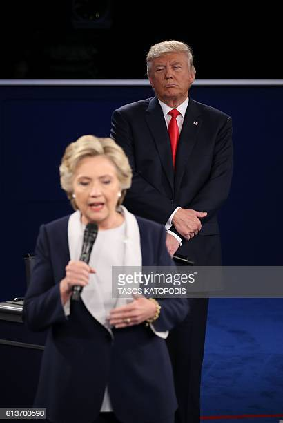 US Republican presidential candidate Donald Trump listens to US Democratic presidential candidate Hillary Clinton during the second presidential...