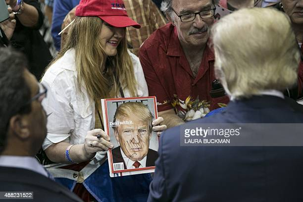 US Republican presidential candidate Donald Trump looks at an freshlyautographed copy of his Time Magazine cover after a campaign rally at the...