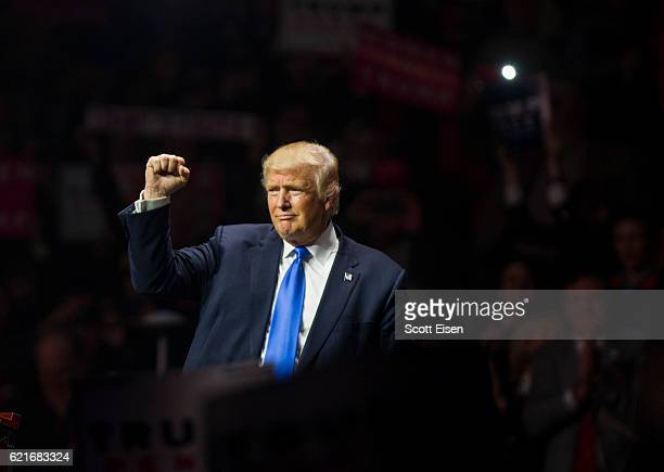 Republican presidential candidate Donald Trump makes a fist at the end of his rally at the SNHU Arena on November 7 2016 in Manchester New Hampshire...