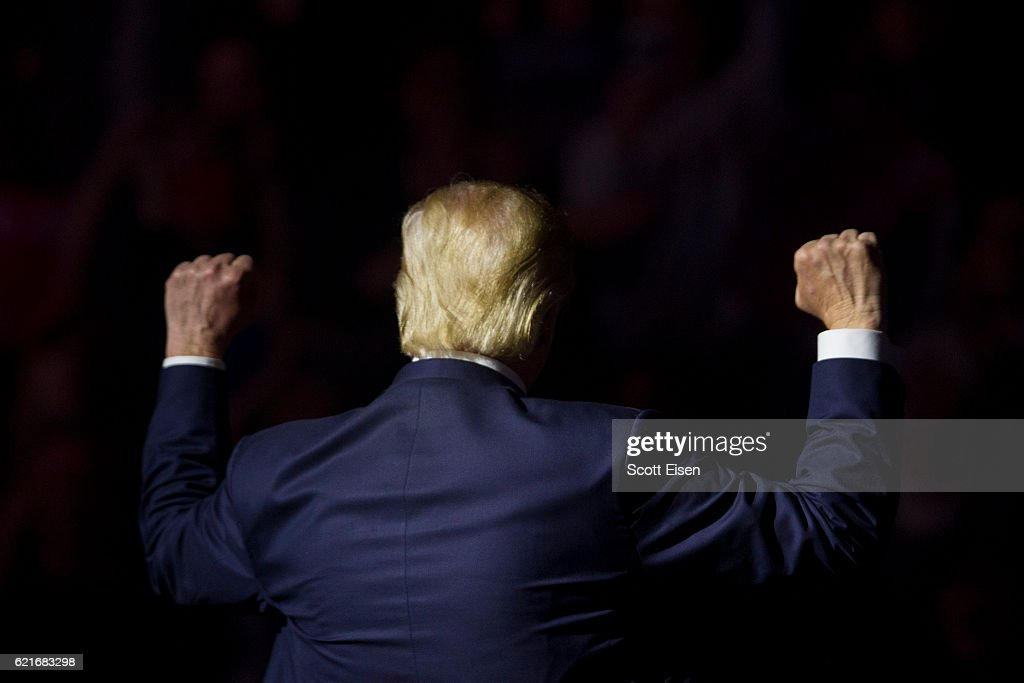Republican presidential candidate Donald Trump makes gestures to supporters at the end of his rally at the SNHU Arena on November 7, 2016 in Manchester, New Hampshire. With one day until the election, both candidates and their surrogates are holding campaign rallies in battleground states across the nation.