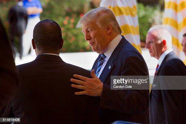 Republican presidential candidate Donald Trump pats Dr Ben Carson on the back after his endorcement announced at MaraLago Trump's resort in Palm...
