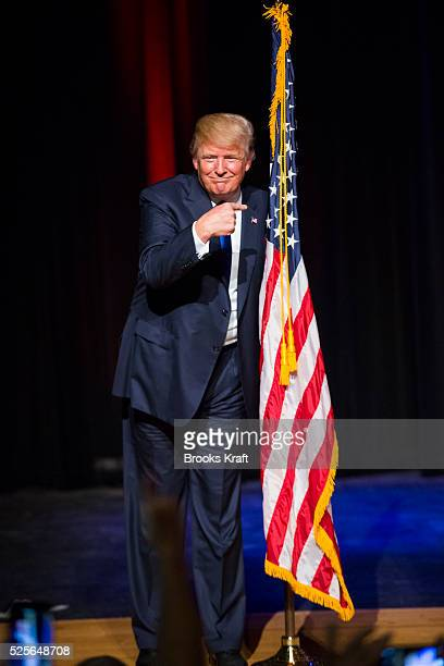 Republican presidential candidate Donald Trump points to an American flag while attending a town hall in Derry NH