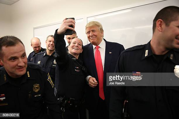 Republican presidential candidate Donald Trump poses for a photo with an officer while visiting the Manchester Police Department during a shift...