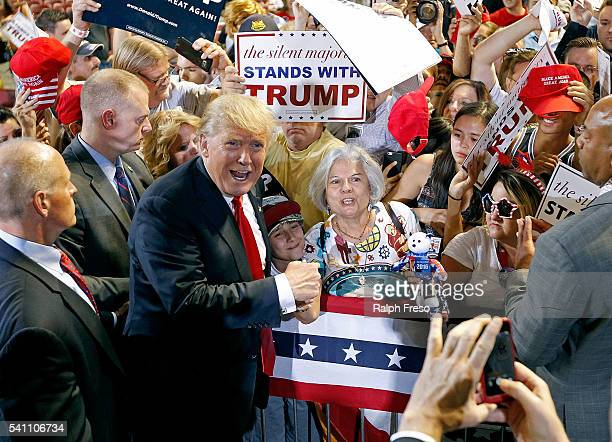 Republican presidential candidate Donald Trump poses for a photo with supporter Diana Brest during a campaign rally on June 18 2016 in Phoenix...