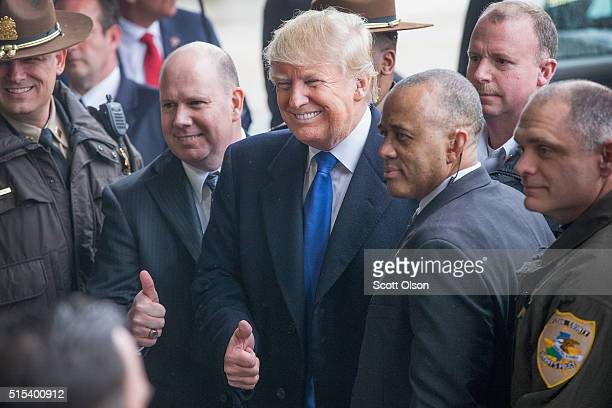 Republican presidential candidate Donald Trump poses with law enforcement officers following a rally at the Central Illinois Regional Airport on...