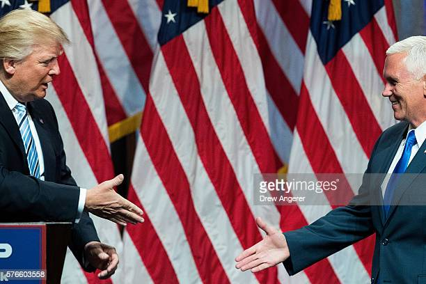 Republican presidential candidate Donald Trump prepares to shake hands with his newly selected vice presidential running mate Mike Pence governor of...