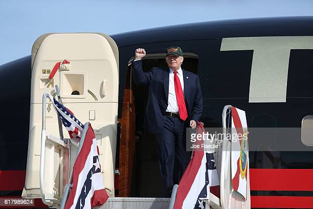 Republican presidential candidate Donald Trump pumps his fist as he steps out of his campaign plane for a campaign rally at the Million Air Orlando...