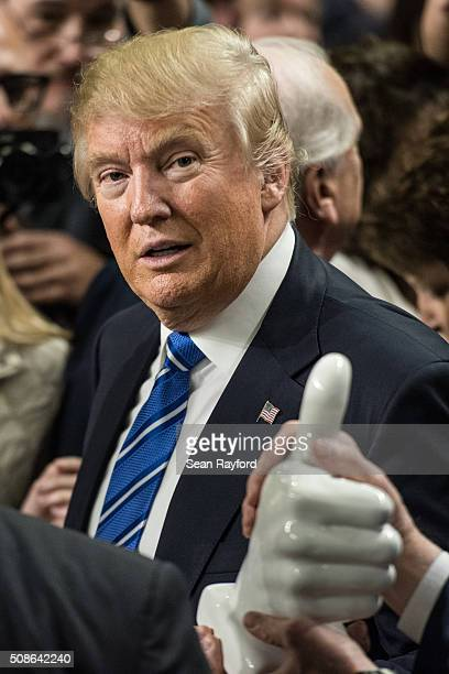 Republican presidential candidate Donald Trump receives a giant thumbs up as a gift from a supporter at a campaign rally February 5 2016 in Florence...
