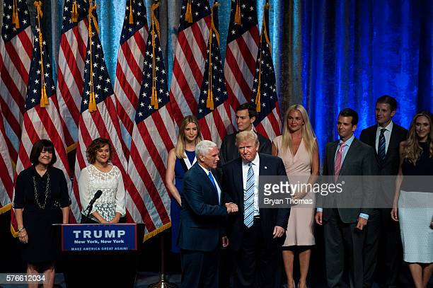Republican presidential candidate Donald Trump right shakes hands with his vice presidential running mate Indiana Gov Mike Pence left as family...