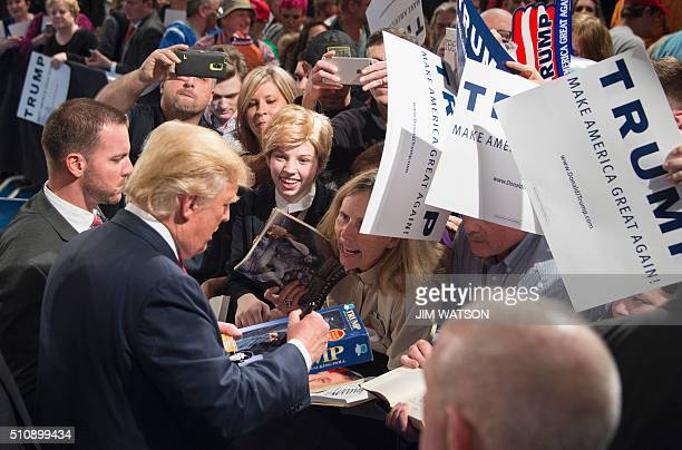 Republican presidential candidate Donald Trump signs a Trump doll for a girl dressed in costume like him during a campaign rally in Sumter South...