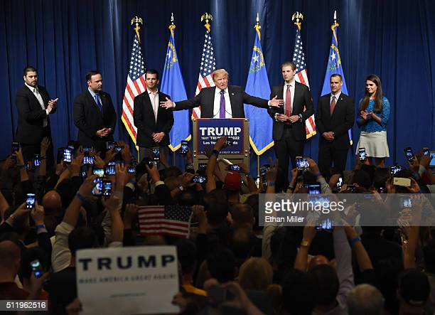 Republican presidential candidate Donald Trump speaks as his sons Donald Trump Jr and Eric Trump look on during a caucus night watch party at the...