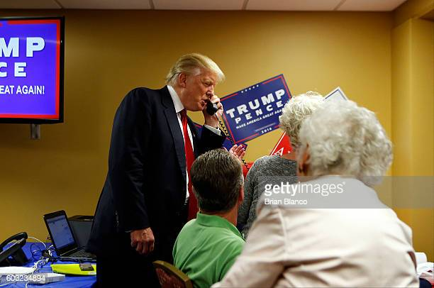 Republican presidential candidate Donald Trump speaks to a caller on the other end of the phone line as volunteers man a phone bank prior to a rally...