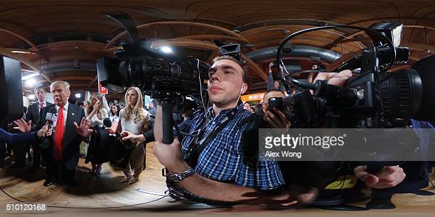 Republican presidential candidate Donald Trump speaks to members of the media in the spin room as his wife Melania looks on after a CBS News GOP...