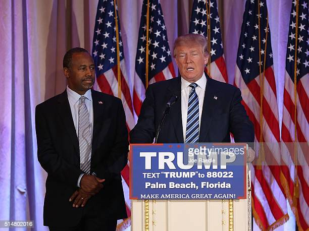 Republican presidential candidate Donald Trump stands with former presidential candidate Ben Carson as he receives his endorsement at the MarALago...