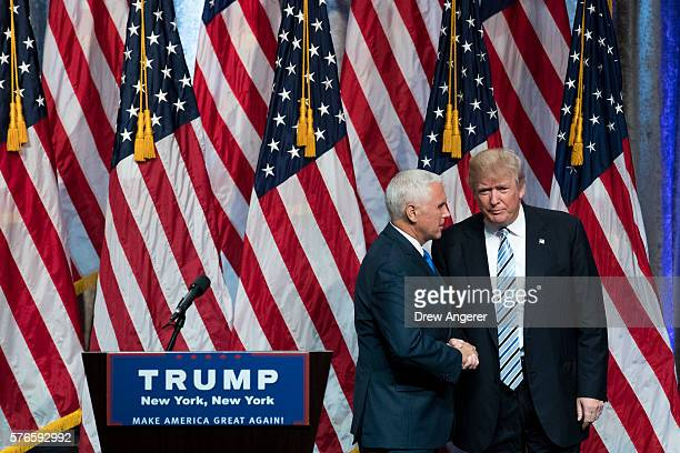 Republican presidential candidate Donald Trump stands with his newly selected vice presidential running mate Mike Pence governor of Indiana at the...