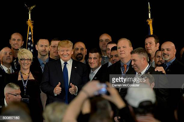Republican presidential candidate Donald Trump stands with law enforcement officers after receiving the endorsement of the New England Police...