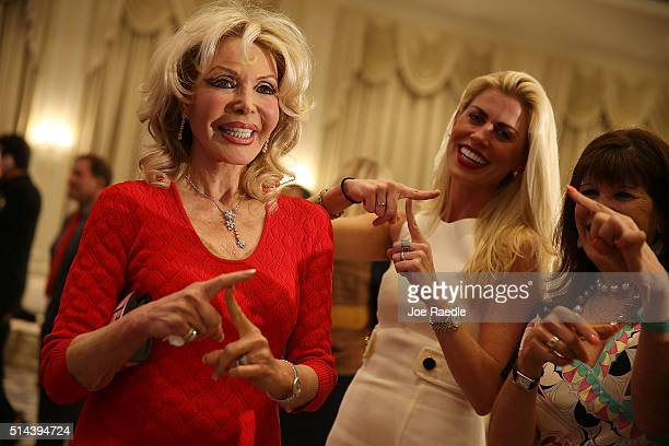 Republican presidential candidate Donald Trump supporters make a T with their fingers as they wait for him to arrive for a press conference at the...