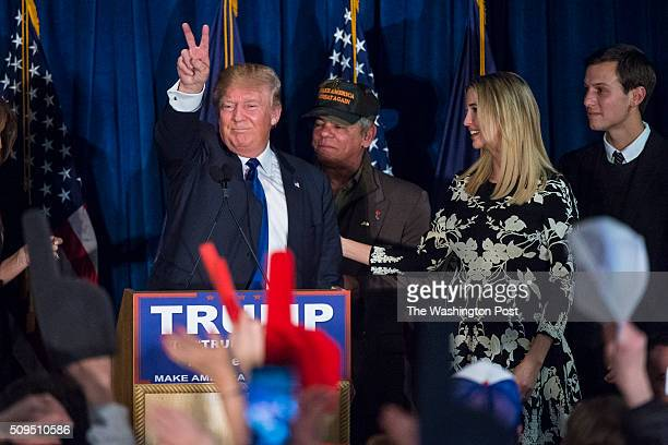 Republican presidential candidate Donald Trump surrounded by family and friends gives the peace sign as he celebrates his victory at a New Hampshire...