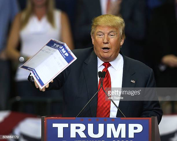 Republican presidential candidate Donald Trump tosses a paper into the crowd as he speaks during a campaign rally at the University of South Florida...