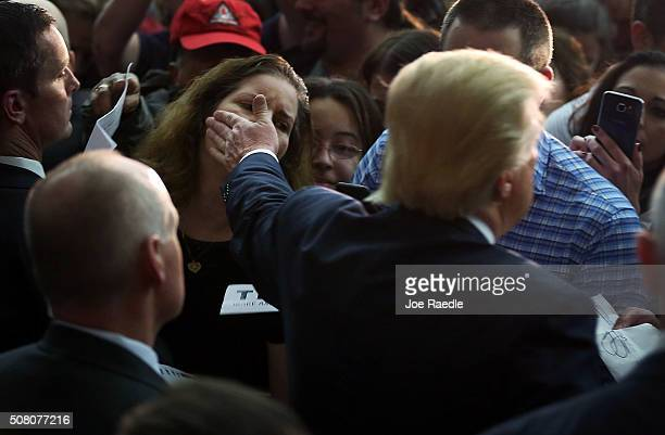 Republican Presidential candidate Donald Trump touches the face of a supporter as he greets people during a campaign event at Hampshire Hills...