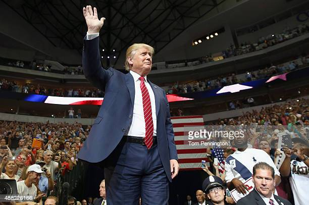 Republican presidential candidate Donald Trump waves to the audience gathered for a campaign rally at the American Airlines Center on September 14...