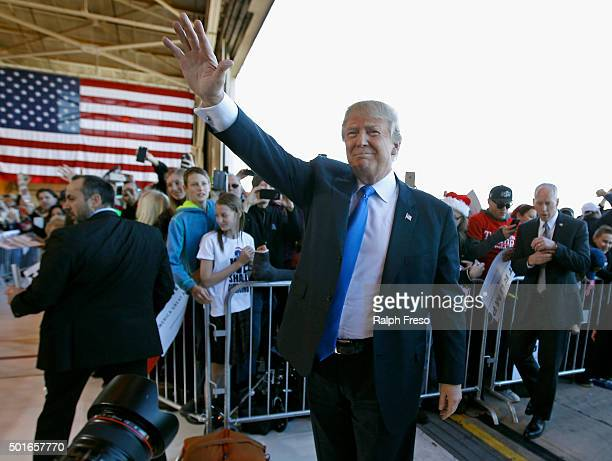 Republican presidential candidate Donald Trump waves to the crowd as he arrives at a campaign event at the International Air Response facility on...