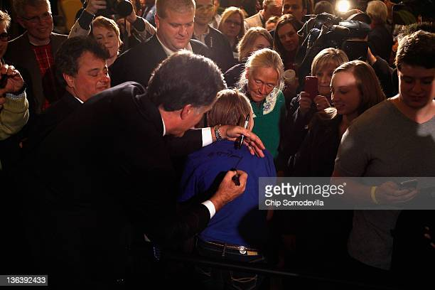 Republican presidential candidate former Massachusetts Gov Mitt Romney signs a girl's tshirt at the Hotel Fort Des Moines on the night of the Iowa...