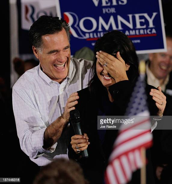 Republican presidential candidate former Massachusetts Gov Mitt Romney has a laugh with South Carolina Gov Nikki Haley after she misspoke during a...