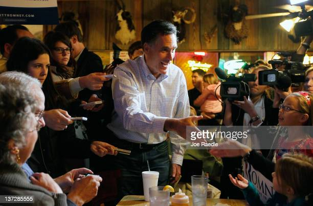 Republican presidential candidate former Massachusetts Gov Mitt Romney talks with people as he visits Hudson's Smokehouse on January 18 2012 in...