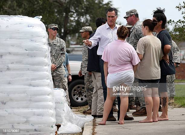 Republican presidential candidate former Massachusetts Gov Mitt Romney points to a pallet of ice as he talks to victims of Hurricane Isaac on August...