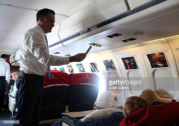 Republican presidential candidate former Massachusetts Gov Mitt Romney uses his iPhone to make a video of staff members who are sleeping aboard his...