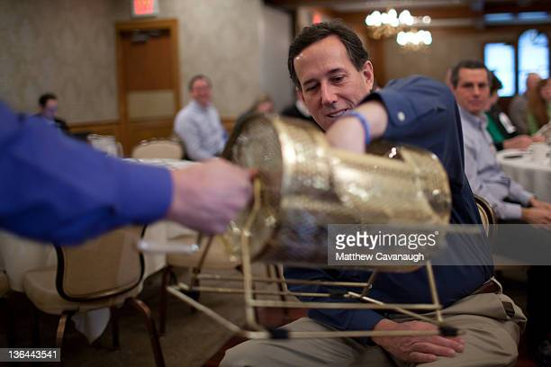 Republican Presidential candidate former US Sen Rick Santorum picks the winner of a raffle prior to speaking at a Rotary Club breakfast in Manchester...