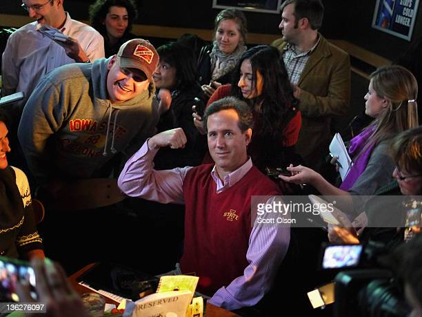 Republican presidential candidate former U.S. Senator Rick Santorum poses for a picture while hosting a Pinstripe Bowl watch party at Buffalo Wild...