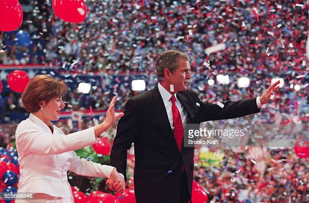 Republican presidential candidate George W. Bush and his wife Laura wave to supporters as confetti falls around them at the 2000 Republican National...