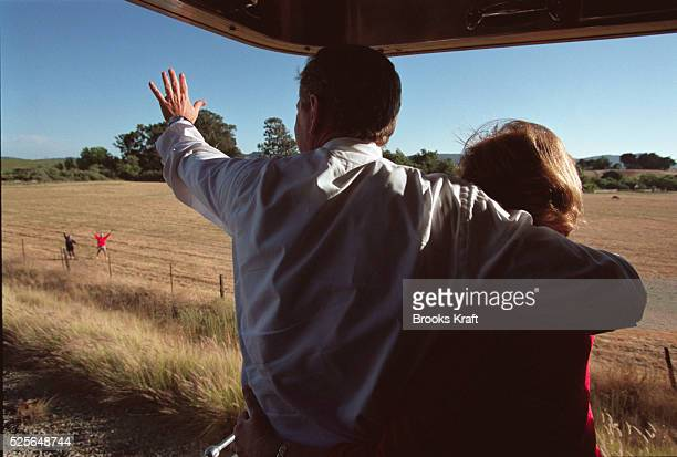 Republican presidential candidate George W Bush and his wife Laura wave to supporters as they campaign by train through California Texas Governor...