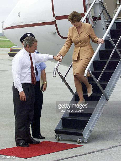 Republican presidential candidate George W Bush helps his wife Laura down the steps of her plane to give her a kiss goodbye as she leaves for the...