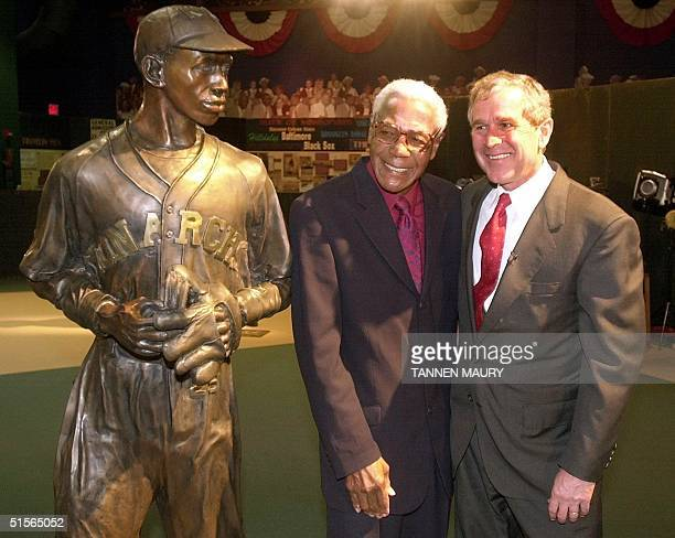 Republican presidential candidate George W. Bush poses next to a statue of Negro league baseball player Satchel Paige with former Negro League star...