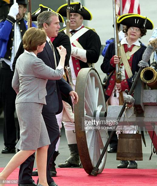 Republican presidential candidate George W Bush walks with his wife Laura past an honor guard wearing Revolutionaryera uniforms after arriving at the...