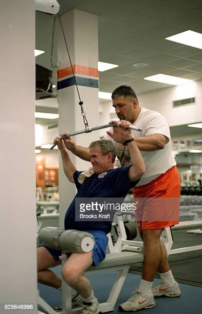Republican presidential candidate George W Bush works out with a personal trainer in a gym at Clemson University Texas Governor Bush took a break...