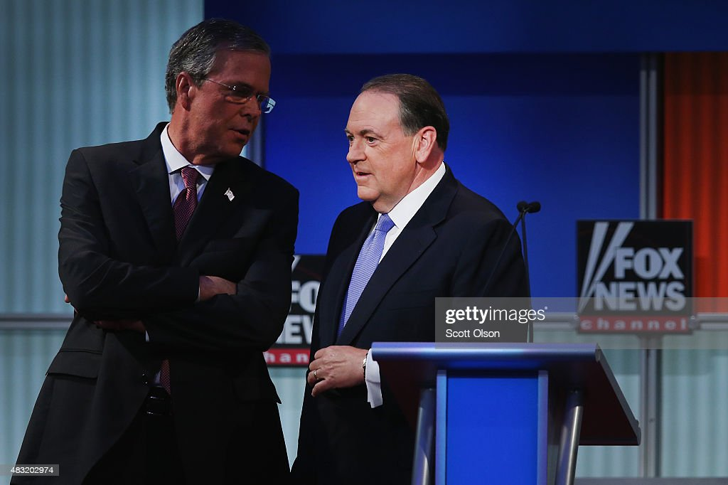 Republican presidential candidate Jeb Bush and Mike Huckabee chat during a break in the first Republican presidential debate hosted by Fox News and Facebook at the Quicken Loans Arena on August 6, 2015 in Cleveland, Ohio. The top ten GOP candidates were selected to participate in the debate based on their rank in an average of the five most recent political polls.