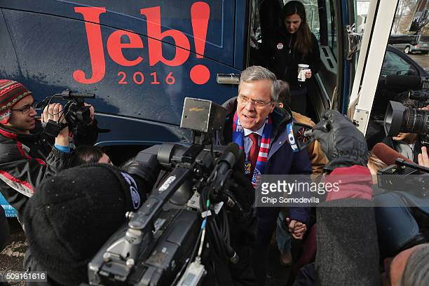 Republican presidential candidate Jeb Bush wades into a crowd of television cameras after stepping off his campaign bus outside the polling place at...