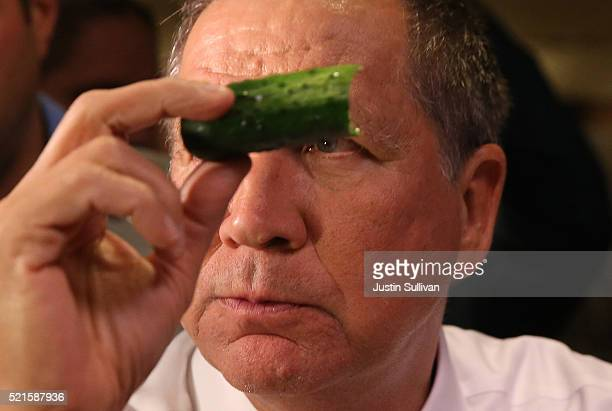 Republican presidential candidate John Kasich eats a pickle while having lunch at PJ Bernstein's Deli Restaurant on April 16 2016 in New York City...