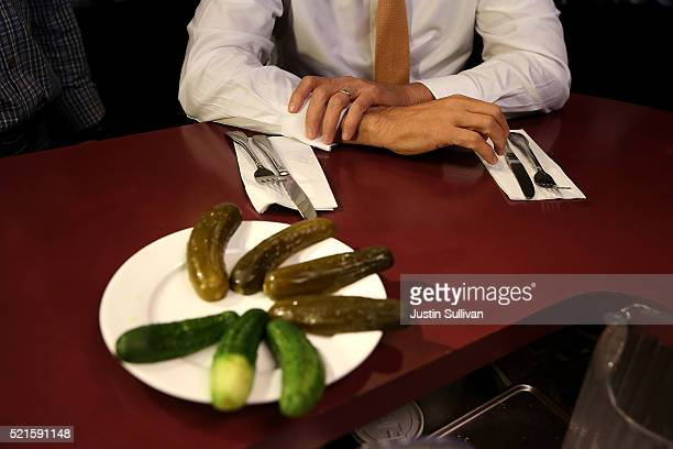 Republican presidential candidate John Kasich prepares to eat pickles while having lunch at PJ Bernstein's Deli Restaurant on April 16 2016 in New...