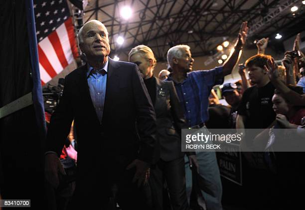 Republican presidential candidate John McCain his wife Cindy and Florida Governor Charlie Crist wave goodbye to supporters at the end of a campaign...