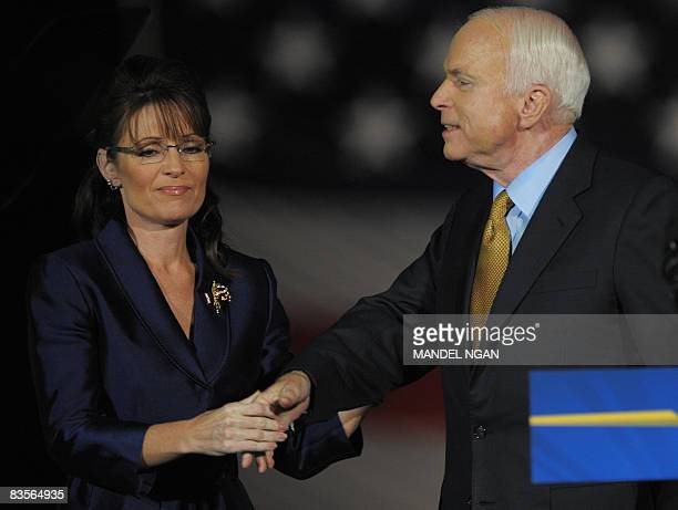 Republican presidential candidate John McCain holds the hand of running mate Sarah Palin after hugging her as he concedes defeat during his election...