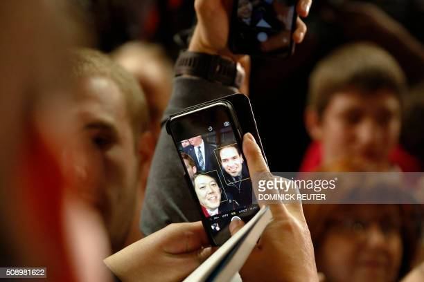 TOPSHOT Republican presidential candidate Marco Rubio takes a selfie with a supporter during a Super Bowl watch party at Ultimate Sports Academy...