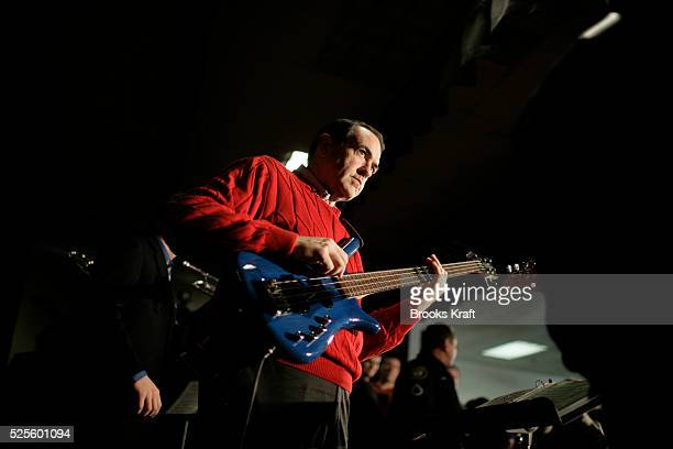 Republican presidential candidate Mike Huckabee plays a bass guitar during a campaign event at the middle school of Londonderry New Hampshire