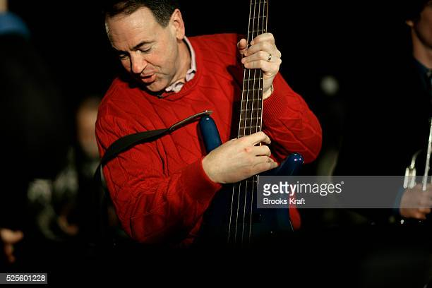 Republican presidential candidate Mike Huckabee plays a bass guitar during a campaign event at the middle school of Londonderry